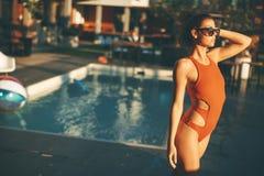Barnet bantar kvinnan som kopplar av vid simbassängen Arkivfoton