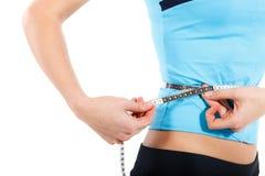 Barnet bantar kvinnan som mäter hennes mage Arkivbild