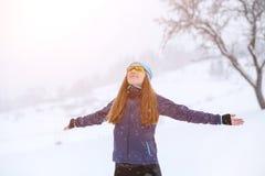 Barnet bantar kvinnan som tycker om snöig väder i vinter Royaltyfri Fotografi