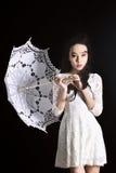 Barnet bantar modellen i ljus sommarklänning med ett filigranparaply som poserar i studio Svart bakgrund royaltyfri bild