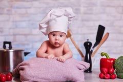 Barnet behandla som ett barn flickan ligger på köksbordet i en kocks lock - bredvid honom är grönsaker, spansk peppar, rädisan, b fotografering för bildbyråer