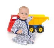 Barnet behandla som ett barn lyckligt sammanträde för pojkelitet barn med den stora leksakbillastbilen Royaltyfri Foto