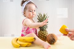Barnet behandla som ett barn nå citronen royaltyfri bild