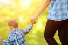 Barnet behandla som ett barn rymma en vuxen hand för ` s Fader och son på en gå T Royaltyfri Bild