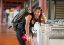 Barnet belastade och oroade den asiatiska kinesiska kvinnan på den trötta flygplatsen, och det ledsna saknade flyget eller lida royaltyfria foton