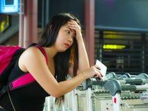 Barnet belastade och oroade den asiatiska kinesiska kvinnan på den trötta flygplatsen, och det ledsna saknade flyget eller lida royaltyfri foto