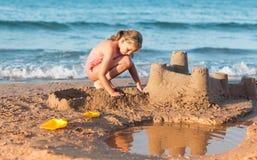 Barnet bygger sandslotten på stranden Royaltyfri Fotografi
