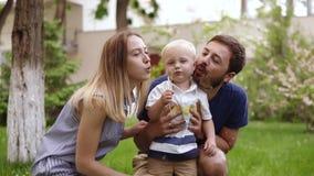 Barnet caucasian par tar tid med deras son Avla med ett hållande barn för skägg med händer Samman med moder stock video