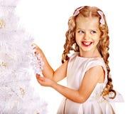 Barnet dekorerar den vita julgranen. Arkivfoton