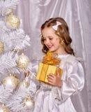 Barnet dekorerar den vita julgranen Royaltyfri Foto