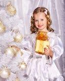 Barnet dekorerar julgranen. Arkivfoton