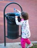 Barnet deltar i återvinning i parkera i vårtid Arkivfoton