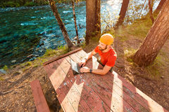 Barnet den lyckade skäggiga mannen, sittande tabell vid floden och arbetar på minnestavlan, utomhus Royaltyfri Fotografi