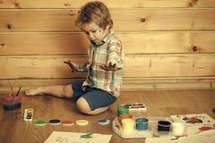 Barnet drar Barn med kulöra händer, gouachemålarfärger och teckningar royaltyfri foto