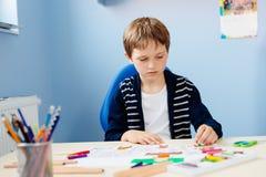 Barnet drar en pastellfärgad teckning av hans lärare i skolagrupp royaltyfri fotografi