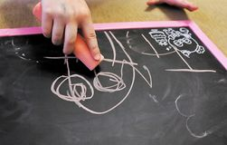 Barnet drar krita på en svart tavla arkivbild