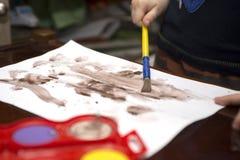 Barnet drar målarfärger på ett vitt ark av papper lego för hand för byggnadsbegreppskreativitet upp väggen royaltyfria bilder