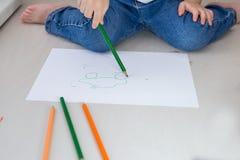 Barnet drar med kulöra blyertspennor på ett vitt stycke av papper Royaltyfria Foton