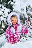 Barnet, en flicka som spelar lyckligt i snön Arkivfoto