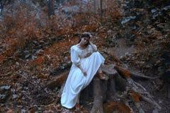 Barnet en prinsessa med mycket långt hår sitter på en stor stubbe som från räkningen av Vogue Brutally vänta på ett mirakel royaltyfria bilder