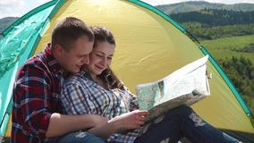 Barnet enloved turist- par som kramar, medan kontrollera deras rutt med den pappers- översikten arkivfilmer