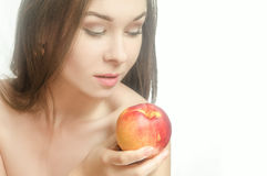 Barnet erbjuder kvinnan med en persika i hennes hand Arkivfoto