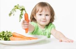 Barnet erbjuder morötter Arkivbild