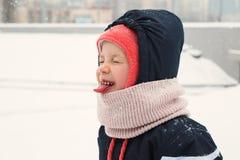 Barnet fångar snön med hans mun royaltyfri foto