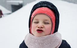 Barnet fångar snön med hans mun royaltyfria bilder