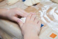 Barnet förbereder degen av mjöl för pastabakelsebröd Arkivbilder