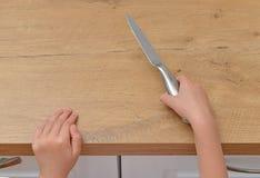 Barnet försöker att få en kökkniv Fotografering för Bildbyråer