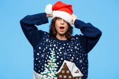 Barnet förvånade den härliga brunettflickan i knited tröja och julhatt över blå bakgrund royaltyfri fotografi