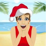 Barnet förvånade kvinnan som bär den santa hatten på stranden, jultema royaltyfri illustrationer