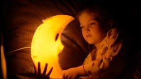 Barnet faller sovande under en lampa stock video