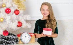 Barnet firar jul hemma Favorit- dag av året Ungeflicka nära asken för gåva för håll för julträd Tid som ska öppnas arkivbilder