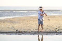 Barnet fiskar på stranden på sjösidan Fotografering för Bildbyråer