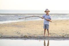 Barnet fiskar på stranden på sjösidan Arkivfoton