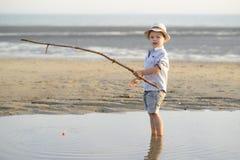 Barnet fiskar på stranden på sjösidan Royaltyfri Fotografi