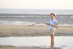 Barnet fiskar på stranden på sjösidan Royaltyfria Foton