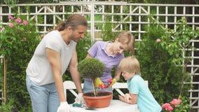 Barnet fostrar att arbeta i trädgården framme eller bakgården med hennes två gulliga lilla barn arkivfilmer