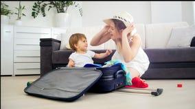 Barnet fostrar att ha gyckel med hennes litet barnson, medan packa resväskan Fotografering för Bildbyråer