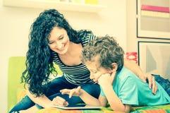 Barnet fostrar att ha gyckel som lär med sonen som använder minnestavlan på säng Royaltyfri Bild