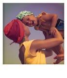 Barnet fostrar att krama hennes dotter på stranden Lycka- och sinnesrörelsebegrepp Arkivbilder