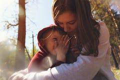 Barnet fostrar att krama hennes lilla son Arkivfoton
