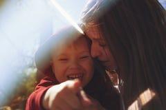 Barnet fostrar att krama hennes lilla son utomhus Fotografering för Bildbyråer