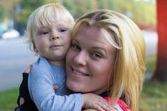 Barnet fostrar att krama hennes son går på Arkivfoto