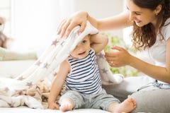 Barnet fostrar att kyssa henne behandla som ett barn att ligga på sängen fotografering för bildbyråer