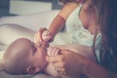 Barnet fostrar att spela med hennes behandla som ett barn pojken i säng Moder som tycker om I fotografering för bildbyråer