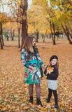 Barnet fostrar att spela med hennes dotter i höst parkerar royaltyfria bilder
