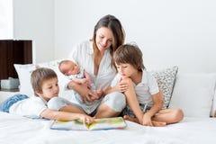 Barnet fostrar, läser en bok till hennes tre barn, pojkar, i vara royaltyfria foton